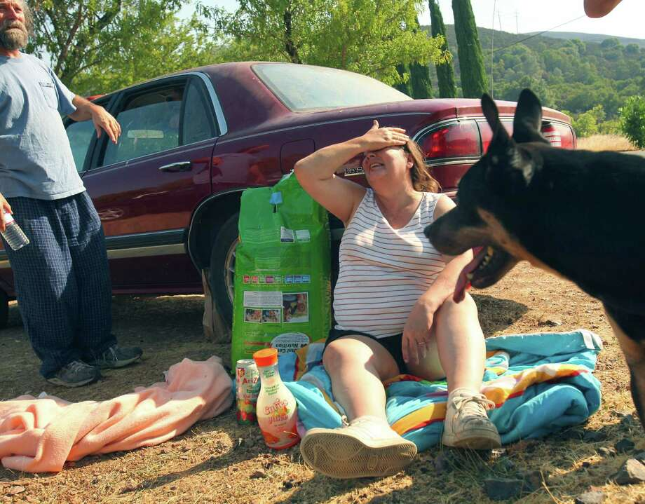 Rita Torre, 47, sits on the side of the road with her dog Puma after driving over a burning log evacuating her home and the Wye fire near Clearlake Oaks, Calif., Monday2. Torre left her home on Spring Valley Road on. Sunday night. The Wye fire had burned about 3,000 acres and was considered to be 25 percent contained Monday. Wildfires burn across the West, threatening hundreds of homes in California and killing a firefighter in Idaho. (AP Photo/The Press Democrat, John Burgess) Photo: Associated Press