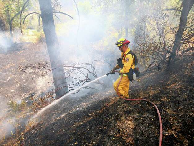 A California Department of Forestry firefighter works on putting out a flare up along Highway 20 on the Wye Fire, near Clearlake Oaks, Calif., Monday, Aug. 13, 2012. Wildfires burn across the West, threatening hundreds of homes in California and killing a firefighter in Idaho. (AP Photo/The Press Democrat, John Burgess) Photo: Associated Press