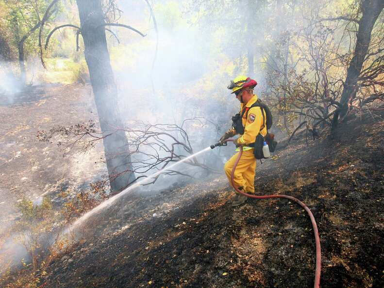 A California Department of Forestry firefighter works on putting out a flare up along Highway 20 on