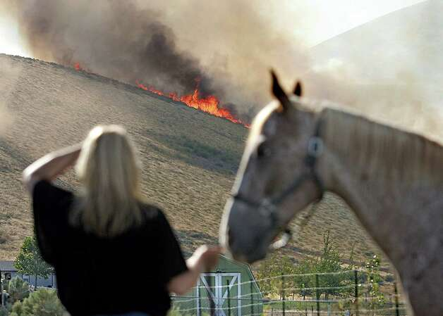 Barb Otte of West Richland holds a neighbor's horse as she watches a line of flames head across Red Mountain in West Richland, Wash.,  late Monday afternoo.  Several of Kelly Arthur-Moore's neighbors rushed to help her pull three horses and other pets out of harms way. Photo: Ap