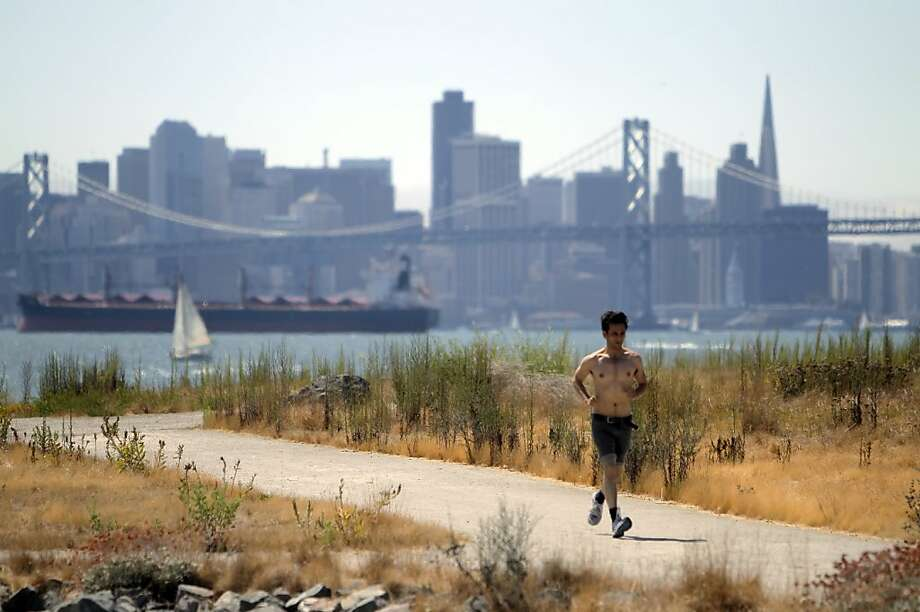 Zebu Recchia of Oakland jogs on one of the trails at Middle Harbor Shoreline Park, which also has views of S.F. Photo: Carlos Avila Gonzalez, The Chronicle