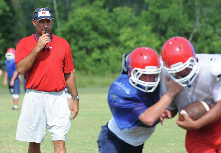 Hardin-Jefferson football coach David Martel, left, instructs players, who met on the school's practice field Friday to drill plays and ready the team to play Anahuac at the Panther's stadium on August 31. Photo taken Friday, August 10, 2012 Guiseppe Barranco/The Enterprise Photo: Guiseppe Barranco, STAFF PHOTOGRAPHER / The Beaumont Enterprise