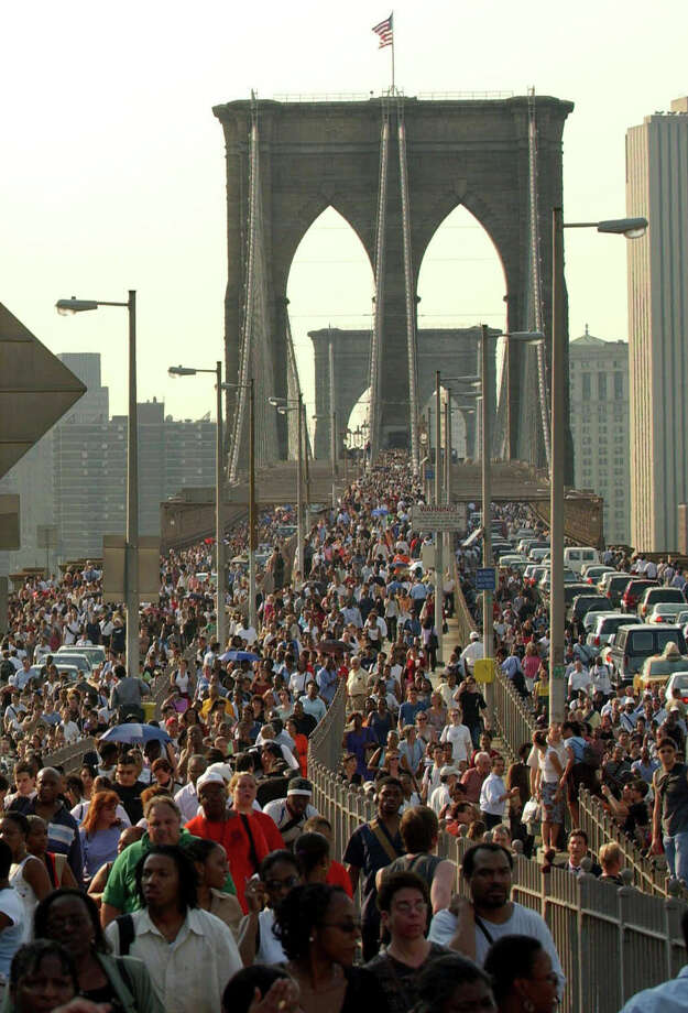 Pedestrians and vehicles cross New York's Brooklyn Bridge after a massive power outage Thursday, Aug. 14, 2003. (AP Photo/New York Post, Chad Rachman)