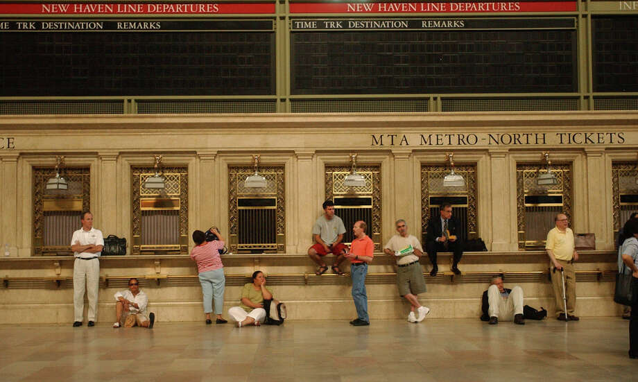 People wait under empty destination boards at Grand Central Terminal in New York after a massive blackout Thursday, Aug. 14, 2003. An extraordinary power blackout hit steamy U.S. and Canadian cities Thursday, stranding people in subways, closing nine nuclear power plants from New York to Michigan and choking streets with workers driven from stifling offices. (AP Photo/Mary Altaffer)