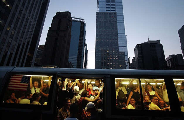 People try to board the back of a crowded Manhattan bus during the power outtage in New York Thursday, Aug. 14, 2003. Buses were packed to capacity after the subway lines closed down during the outtage. (AP Photo/Gregory Bull)