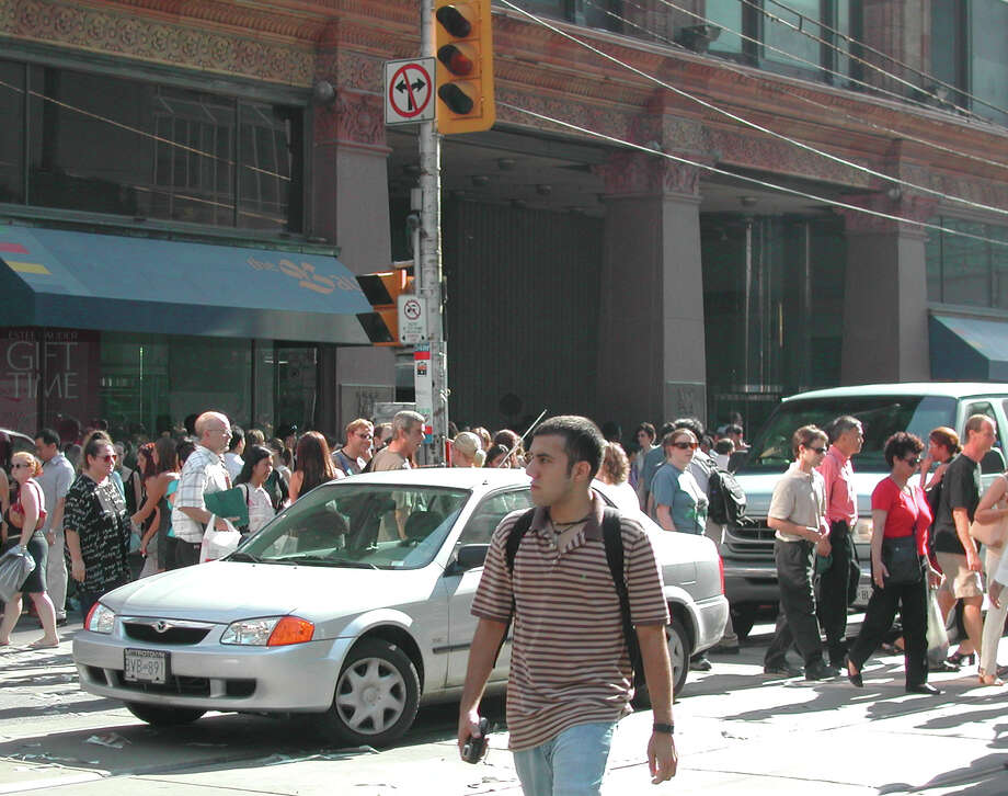 Pedestrians move around cars after traffic lights went out in downtown Toronto, Thursday, Aug. 14, 2003. Traffic, subways, elevators and office buildings shut down following a widespread power outage that included Ontario and parts of the United States. (AP Photo/Ron Poling)