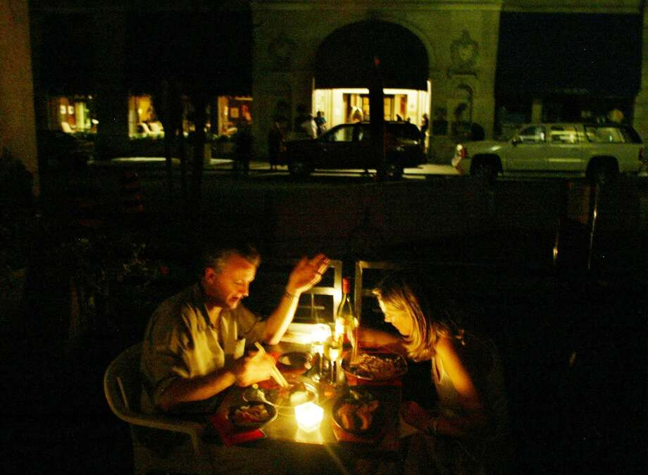 A couple enjoys a candlelight dinner at a downtown Toronto restaurant Thursday, Aug. 14, 2003, during a major power failure. A power blackout hit much of Ontario and the northeastern United States on Thursday afternoon. (AP Photo/CP, Paul Chiasson)
