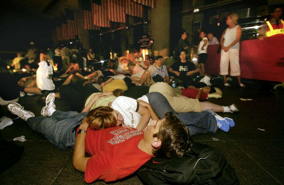 People with no place to go after they were not allowed into their hotel rooms, the Marriott Marquis in New York's Times Square, sleep on the sidewalk outside the hotel early Friday morning Aug. 15, 2003, following a massive power outage that darkened the city. (AP Photo/Joe Kohen)
