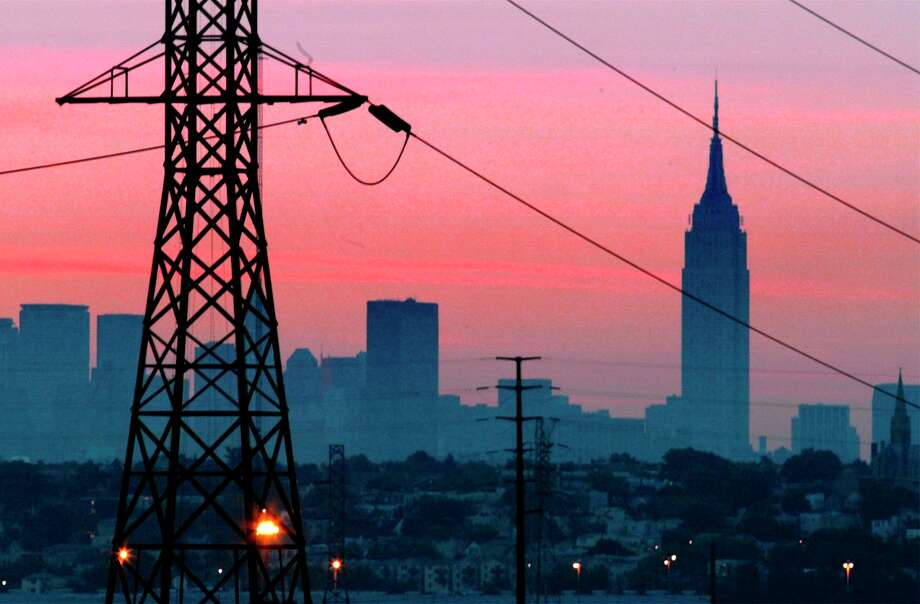 A darkened New York City is visible just before dawn through power lines from Jersey City, N.J., shown in foreground, with some lights visible, Friday, Aug. 15, 2003. (AP Photo/George Widman)