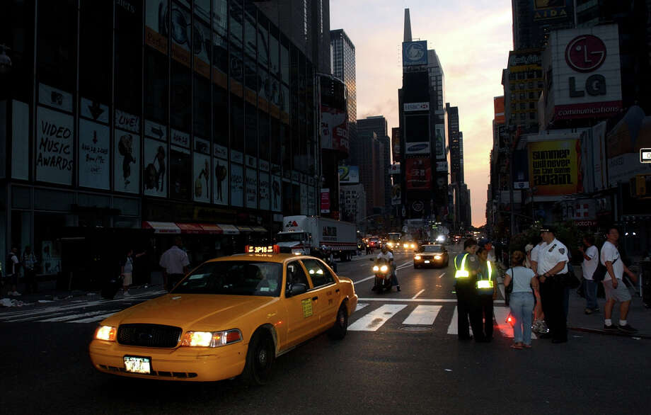 A taxi moves down Broadway through the heart of New York's Times Square at dawn, Friday Aug. 15, 2003.  A massive power blackout left the famed neon lights and most of New York City off the power grid. (AP Photo/Charles Krupa)