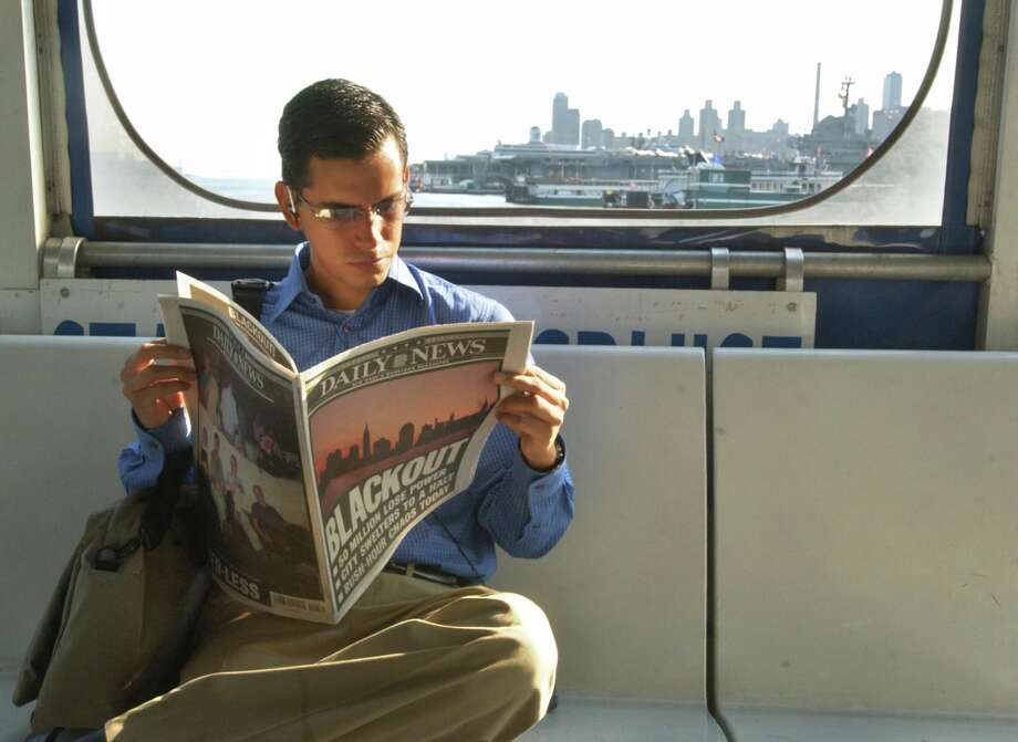 "A man reads a New York newspaper, with a front page banner headline that reads ""Blackout"" as he takes the ferry from New Jersey to midtown New York, seen in background, Friday Aug. 15, 2003.  A massive blackout hit New York and other eastern North American cities Thursday.  (AP Photo/Jacqueline Larma)"