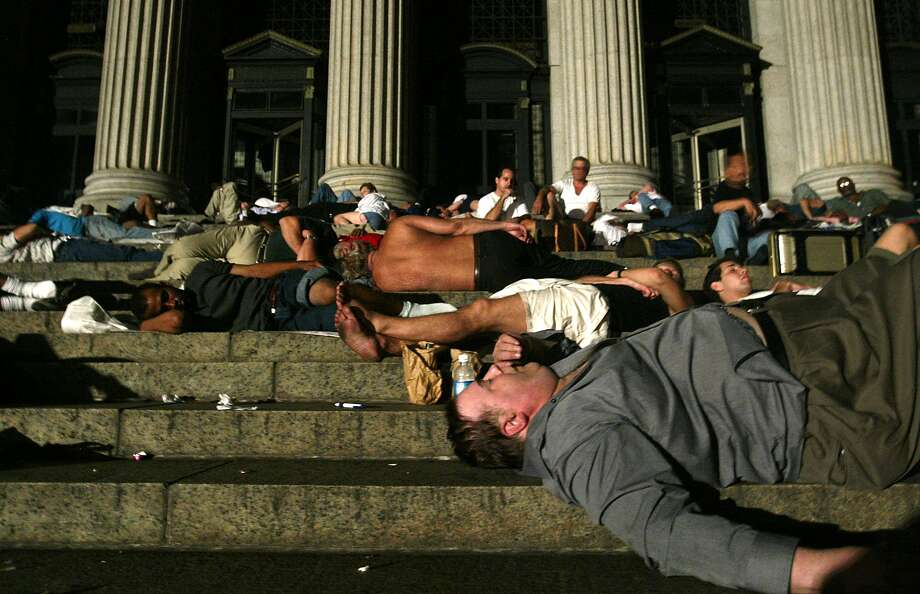 Commuters sleep on the steps of the Post Office on 33rd Street and Eighth Avenue in New York during the early hours of Friday, Aug. 15, 2003 after being stranded by the city's electrical blackout.  (AP Photo/ Mike Appleton)