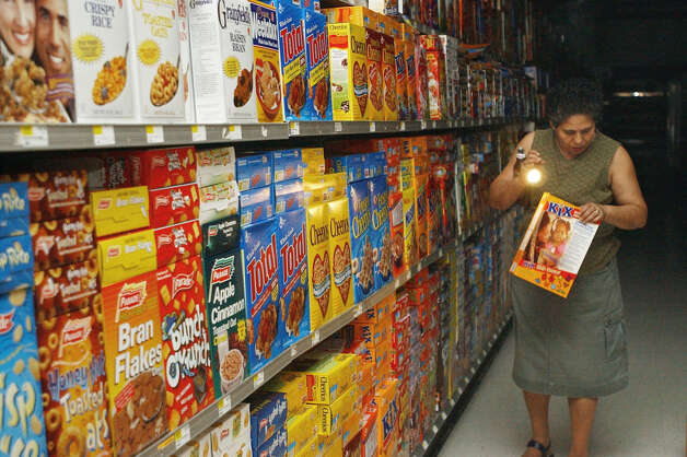 Lucy Ares, of New York, examines a box of breakfast cereal Friday, Aug. 15, 2003 as she shops by flashlight in a downtown Manhattan supermarket which remained without power after a massive blackout which affected parts of the Northeast, Midwest and Canada. (AP Photo/Mary Altaffer)