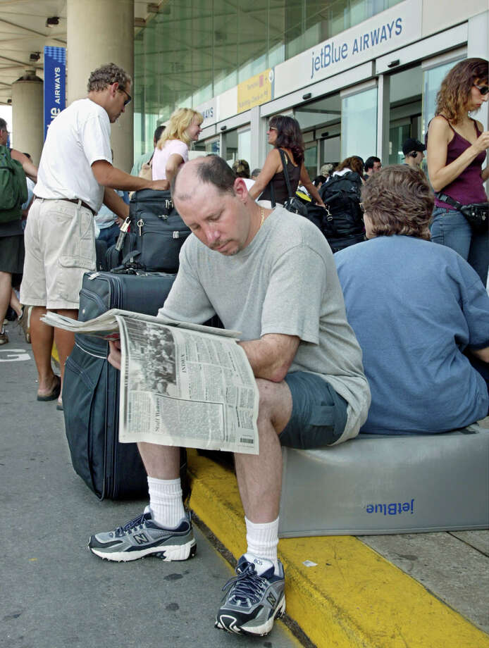 Paul Miller of Plainview, N.Y., reads about the worst power outtage in United States history while lining up outside the JetBlue airways terminal awaiting news of the flight which was to transport Miller and his family to Orlando, Fl., at JFK Airport in the New York borough of Queens, Friday, Aug. 15, 2003.  (AP Photo/Stuart Ramson)