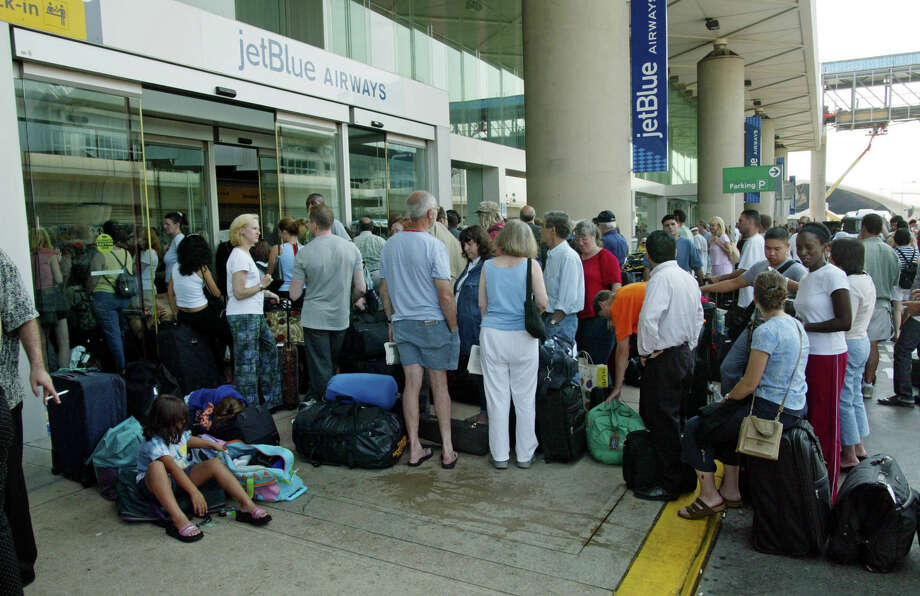 Travellers waiting to check-in line-up outside the JetBlue airways terminal at JFK Airport in the New York borough of Queens, Friday, Aug. 15, 2003. New York was severly crippled overnight during the worst power outtage in United States history. (AP Photo / Stuart Ramson)