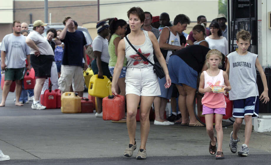 Barb Reinke, with her children Christina, center, and son Eric, head back to their car after purchasing gasoline while more people wait their turn at a gas station Friday, Aug. 15, 2003, in Warren, Mich. Police would not allow cars to line up at the station do to the traffic problems the long lines had caused earlier in the day. (AP Photo/Duane Burleson)