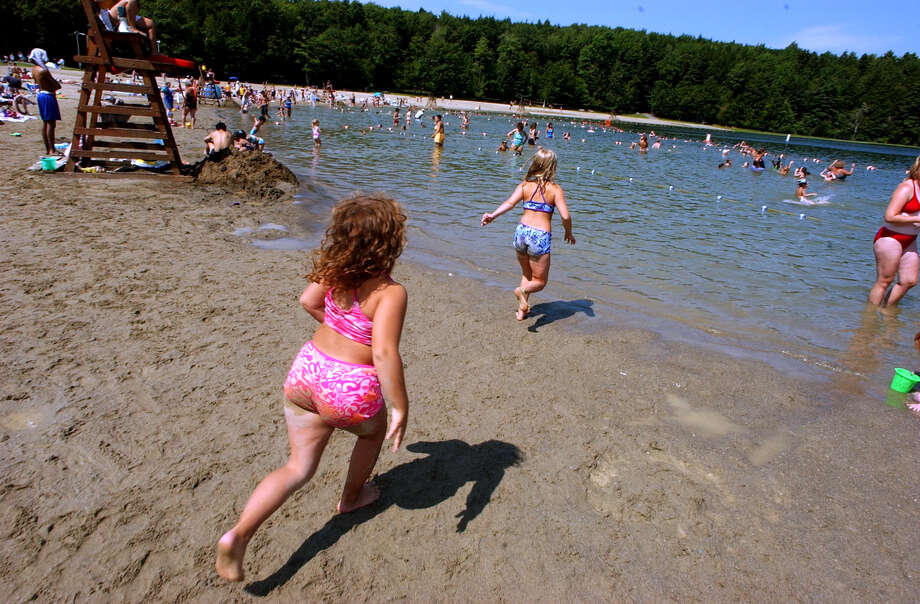 Times Union Staff Photo by Stacey Lauren -- Children run across the beach into the water on a sweltering day Friday at Grafton State Park. Admission into the park was free today because of the blackout yesterday. Friday August 15, 2003 Grafton, NY
