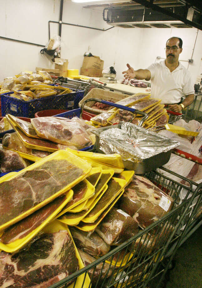 Jose Gonzalez, assistant manager at the Big Apple Meat Market in New York, points to hundreds of pounds of rotten meat Sunday, Aug. 17, 2003, as it waits to be inventoried for insurance purposes following the blackout that hit much of northeastern United States and Canada on Thursday, Aug. 14, 20003. Gonzalez said the blackout cost him tens of thousands of dollars. (AP Photo/Tina Fineberg)