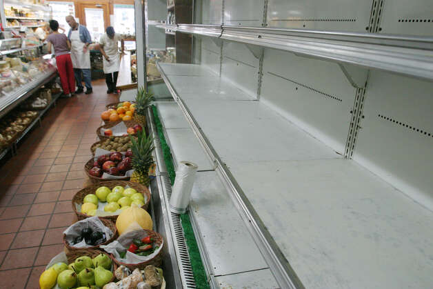 "Shelves that had been filled with perishable goods are now empty at the Ninth Avenue Cheese Market in New York Sunday, Aug. 17, 2003, following Thursday's blackout. Pando Andonopulo, second left, owner of the cheese shop, said he lost hundreds of pounds of cheese, prepared salads and sandwiches. ""It's serious. Maybe I'm not going to be able to pay my rent"",  he said. (AP Photo/Tina Fineberg)"