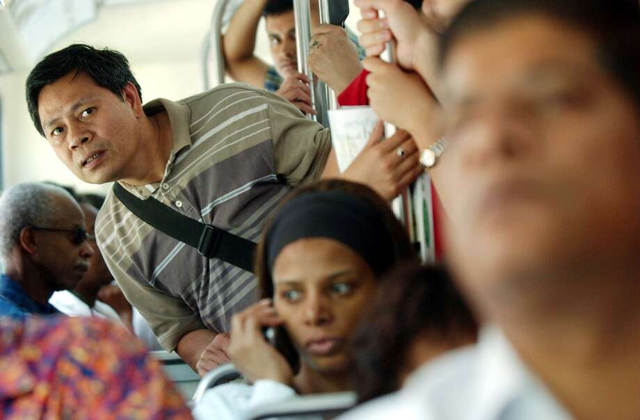 A passenger cranes his neck trying to see the new sign aboard a crammed subway shuttle bus used to replace subway service on the Yonge line in Toronto, Canada on Sunday, Aug. 17, 2003. Subway service is espected to resume Monday morning. (AP PHOTO/Globe & Mail, J.P. Moczulski)
