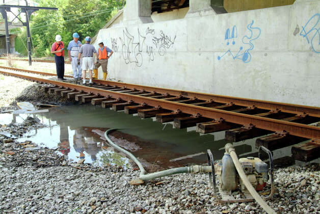 City engineers survey a water main break that shut down a commuter rail line Monday, Aug. 18, 2003 in Cleveland. The water main break happened just a day after the city lifted its warning for residents to boil their water before drinking it. The blackout Thursday had cut off water to a million people in Cleveland for a day. (AP Photo/Steve Cutri)
