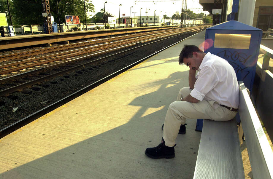 Sergio Laear sits stranded at the Fairfield, Conn., train station platform, waiting for a train during a major power blackout Thursday, Aug. 14, 2003. Laear works in Fairfield, and was trying to get home to Stamford, Conn. (AP Photo/Connecicut Post, Christian Abraham)