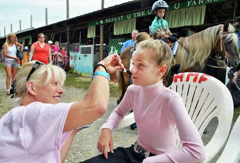 Eleven-year-old Alexis Oliver of Fultonville gets some help with her makeup from stepmother Lisa Walsh before an equestrian competition at the Altamont Fair Tuesday Aug. 14, 2012.  (John Carl D'Annibale / Times Union) Photo: John Carl D'Annibale / 00018832A