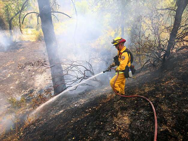 A California Department of Forestry firefighter works on putting out a flare up along Highway 20 on the Wye Fire, near Clearlake Oaks, Calif., Monday, Aug. 13, 2012. Wildfires burn across the West, threatening hundreds of homes in California and killing a firefighter in Idaho. (AP Photo/The Press Democrat, John Burgess) Photo: John Burgess, Associated Press