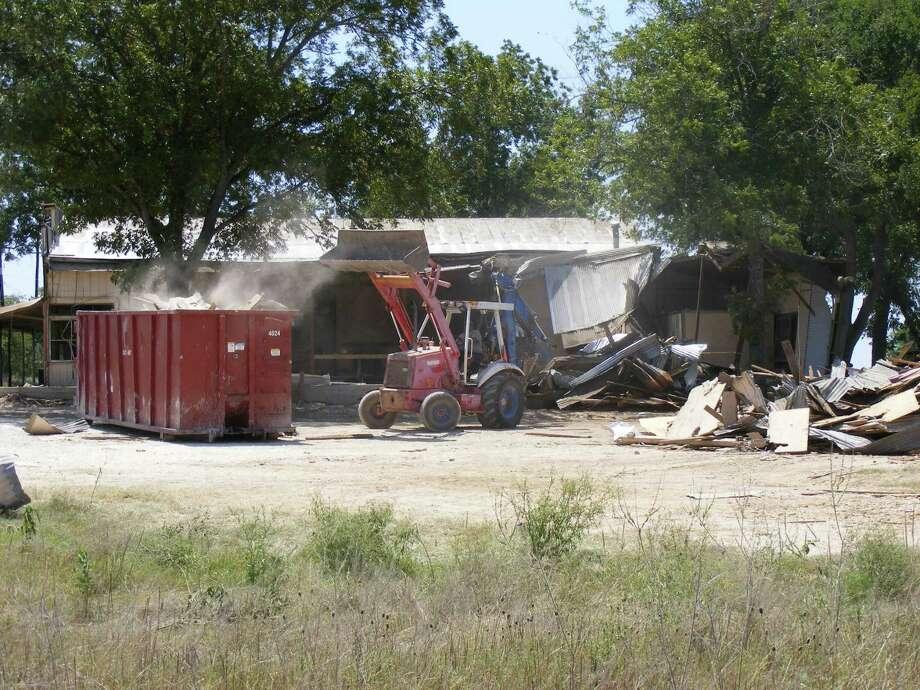 A worker disposes of portions of the demolished Luxello Hall outdoor dance area. Photo: David DeKunder, David DeKunder / NE Herald