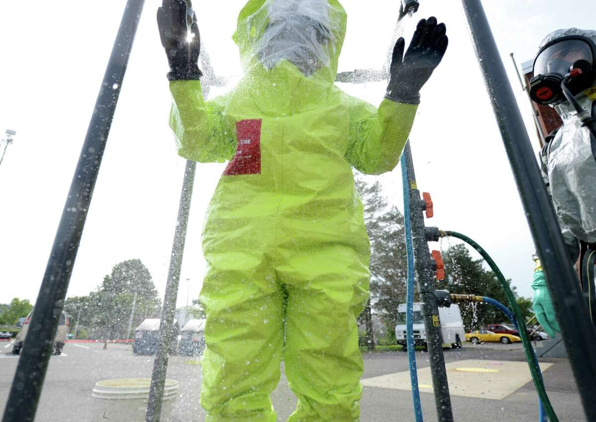 Firefighters and law enforcement personnel gather for a drill at the Watervliet Arsenal in Watervliet, N.Y. Aug 14, 2012. During the drill, a firefighter stands in a water shower for decontamination. (Skip Dickstein/Times Union)