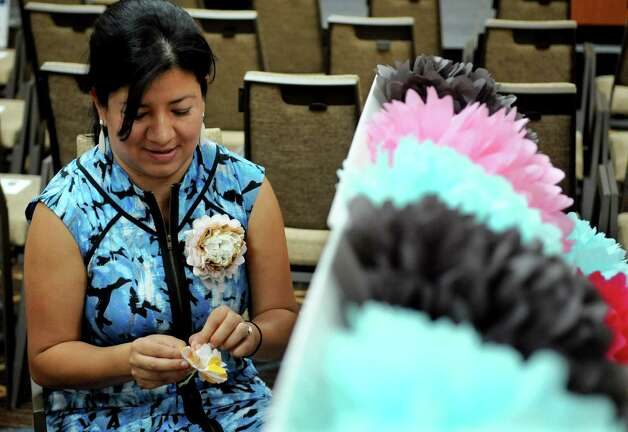 Claudia Suelta makes decorations at the booth for her business, Fiesta Pom Pom, at the Hispanic CHamber of Commerce Business Expo at the Stamford Sheraton on Tuesday, August 14, 2012. Photo: Lindsay Niegelberg / Stamford Advocate