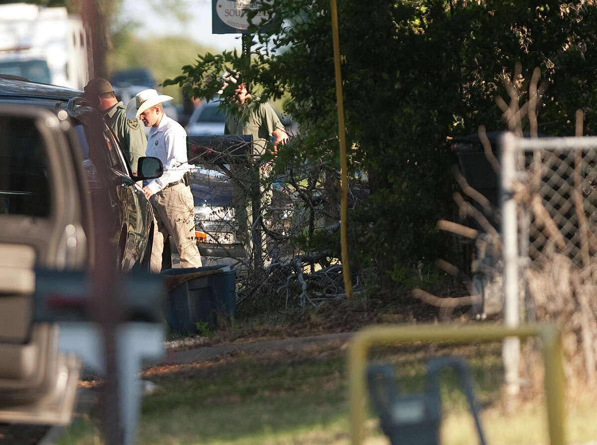 Investigators work the scene of a shooting Tuesday, Aug. 14, 2012, in College Station. The shooting left three dead including a constable.