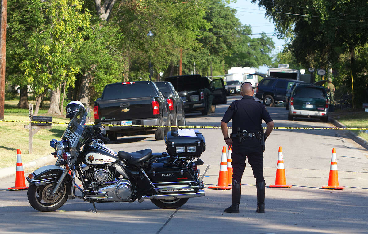 A police officer stands at the scene of a shooting Tuesday, Aug. 14, 2012, in College Station. Residents were escorted to and from their homes allowing to get necessities. The shooting left three dead including a constable.