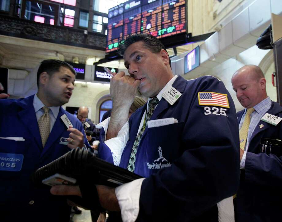 FILE - In a July 31, 2012 file photo trader William McInerney, center, works on the floor of the New York Stock Exchange.  U.S. stocks fell Monday, Aug. 13, 2012 as evidence piled up that the global economic slowdown is dragging on Asia.  (AP Photo/Richard Drew, file) Photo: Richard Drew / AP