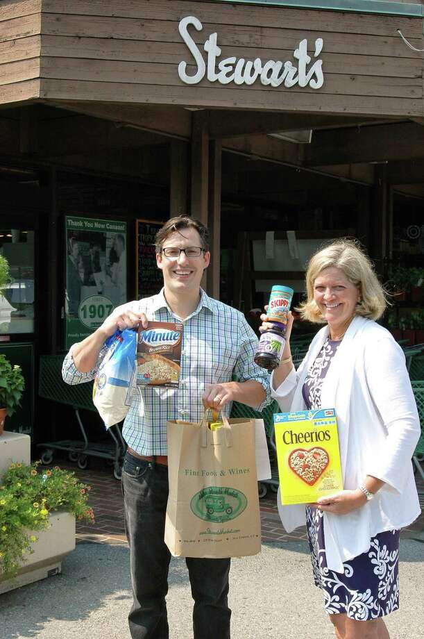Doug Stewart of Walter Stewartís Market and Susan Boston, board member of the New Canaan Food Pantry, show the donation packages and some of the items included in them that are available from the market as part of the Taste of the Town Stroll contribution to the pantry. Photo: Contributed Photo