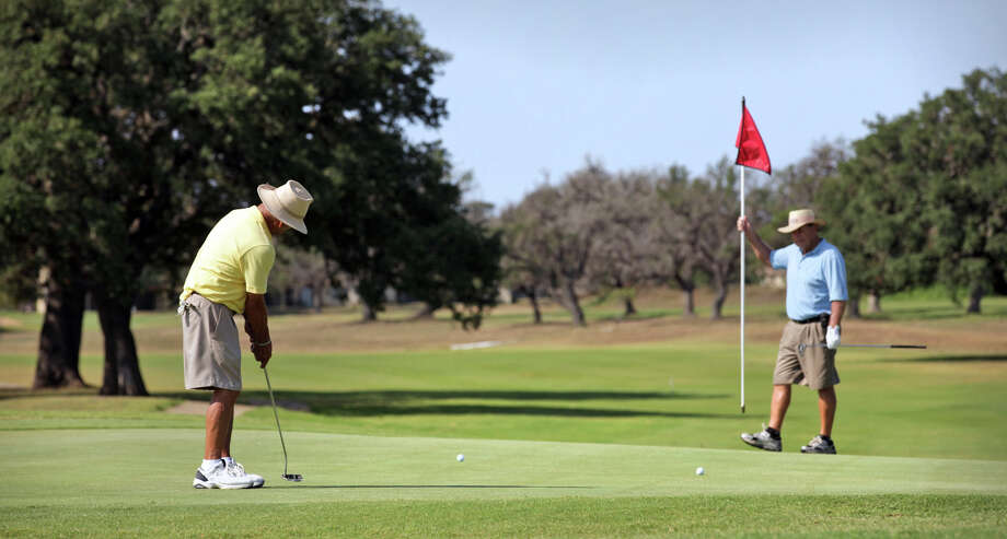 Larry Henson (right) and Roy Rodriguez putt out on hole No. 1 during a recent outing at Flying L Golf Course in Bandera. The course has seen its rounds increase by nearly 1,000 over the last two years. Photo: Bob Owen, San Antonio Express-News / © 2012 San Antonio Express-News