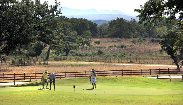 With spectacular views of the Texas Hill Country behind them, golfers putt on the par-3 No. 2 green at the Flying L Ranch Golf Course in Bandera, on Monday, Aug. 13, 2012. Photo: Bob Owen, San Antonio Express-News / © 2012 San Antonio Express-News