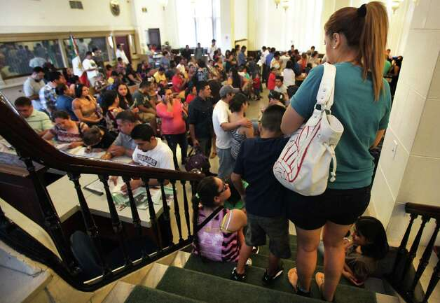 An unidentified boy walks down stairs with his mother to the lobby of the Mexican Consulate in San Antonio where close to 200 wait to complete necessary identification documents to secure immigration status. Tuesday, August 14, 2012. Photo: BOB OWEN, San Antonio Express-News / © 2012 San Antonio Express-News