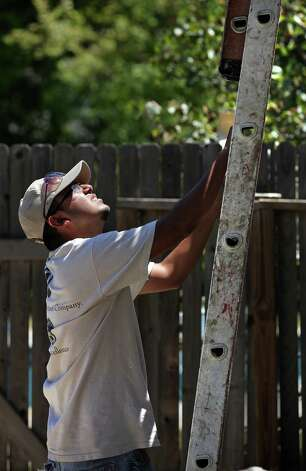 Luis Yanez, 21, who is in the process to complete his identification documents necessary to secure immigration status, paints a house in Terrell Hills at his job. Tuesday, August 14, 2012. Photo: BOB OWEN, San Antonio Express-News / © 2012 San Antonio Express-News