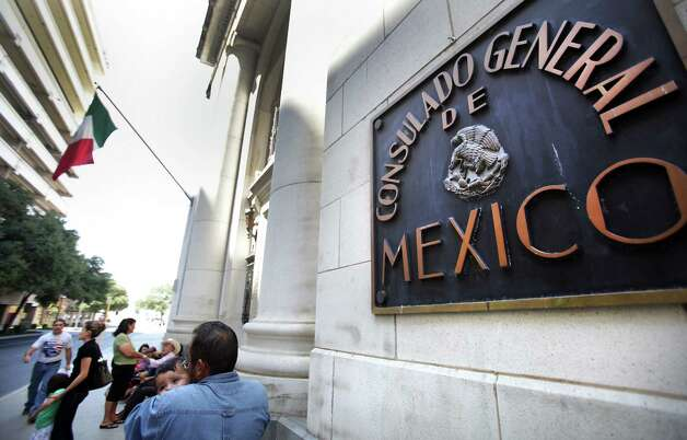 An unidentified man holds an infant in front of the Mexican Consulate in San Antonio where close to 200 were fillilng out forms to complete necessary identification documents to secure immigration status. Tuesday, August 14, 2012. Photo: BOB OWEN, San Antonio Express-News / © 2012 San Antonio Express-News