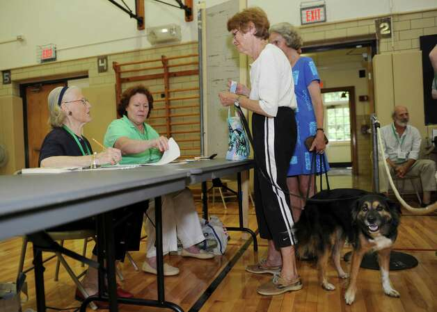 Voter Joan Osgood, a Democrat, and her dog Murphy, receives assistance from poll workers Janice Calkin, left, and Carolyn Austin at Riverside School during the primary Tuesday, Aug. 14, 2012. Photo: Helen Neafsey / Greenwich Time