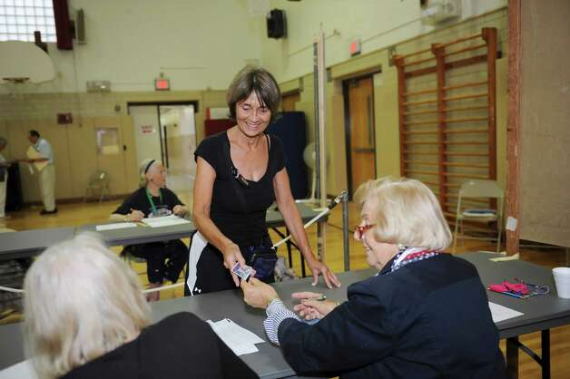 Anne Kampmann gets ready to vote in the primary at Riverside School with help from poll workers Judy Steinberg, left, and Helen Delago Tuesday, Aug. 14, 2012. Photo: Helen Neafsey / Greenwich Time