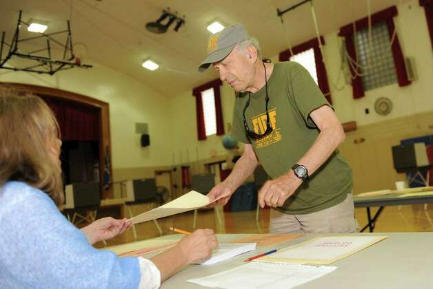 Steven Switzer, a Republican, voting in the primary with help from poll worker Kathy McBain at Riverside School Tuesday, Aug. 14, 2012. Photo: Helen Neafsey / Greenwich Time