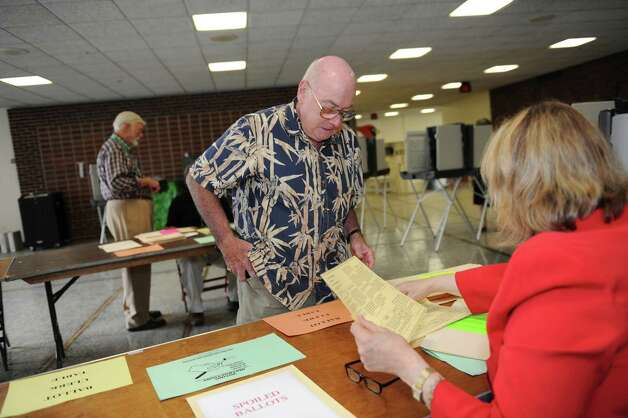 Patrick Waide, a Democrat, prepares to vote in the primary with help from poll worker Christine Edwards at Greenwich High School Tuesday, Aug. 14, 2012. Photo: Helen Neafsey / Greenwich Time