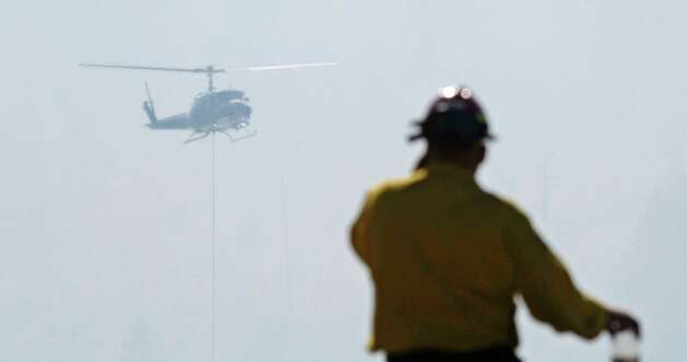 A firefighter looks up at a helicopter dropping water, Tuesday, on state Route 10 near Cle Elum. The fast-moving wildfire has burned 60 homes across nearly 40 square miles of central Washington grassland, timber and sagebrush. No injuries have been reported but more than 400 people have been forced to flee. Photo: Ap
