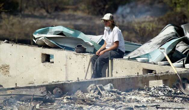 A woman sits on the remains of a home that was destroyed in a wildfire the night before Tuesday on Bettas Road near Cle Elum. The fast-moving wildfire has burned 60 homes across nearly 40 square miles of central Washington grassland, timber and sagebrush. No injuries have been reported but more than 400 people have been forced to flee. Photo: Ap