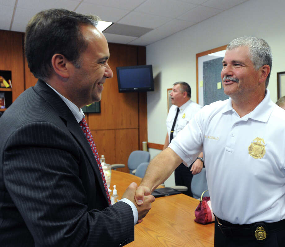 Greenwich First Selectman Peter Tesei, left, shakes hands with James McDonald, after McDonald was appointed Fire Marshal by Tesei and the other two selectmen at Greenwich Town Hall, Tuesday, Aug.14, 2012. Photo: Bob Luckey / Greenwich Time