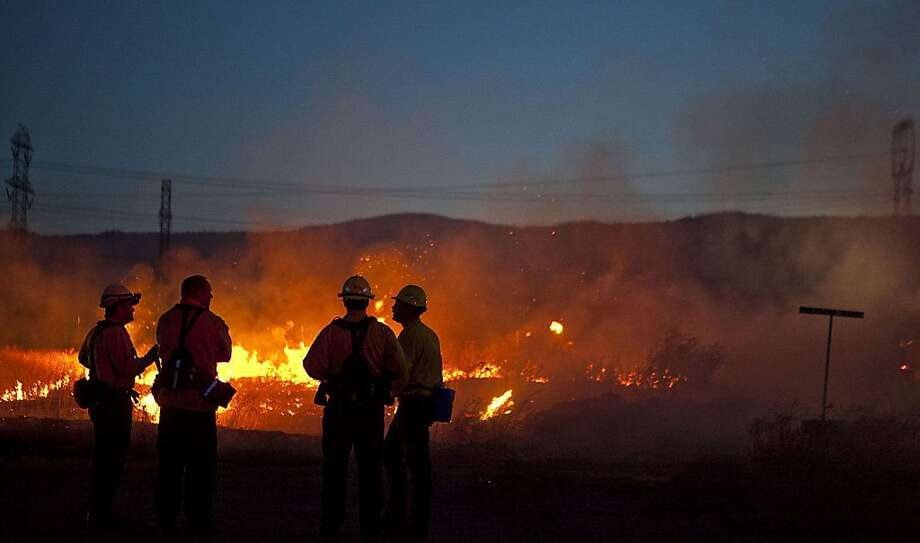 Firefighters wait at the burnout line along near Ellensburg, Washington, as a brush fire fueled by high winds advances east. (Bettina Hansen/Seattle Times/MCT) Photo: Bettina Hansen, McClatchy-Tribune News Service