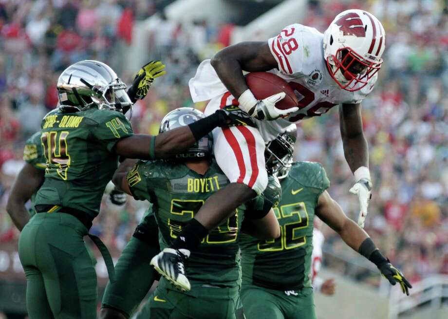 Wisconsin's Montee Ball (28) goes over Oregon's John Boyett (20) and others as he is stopped during the second half of the Rose Bowl NCAA college football game, Monday, Jan. 2, 2012, in Pasadena, Calif. Photo: Matt Sayles, Associated Press / AP