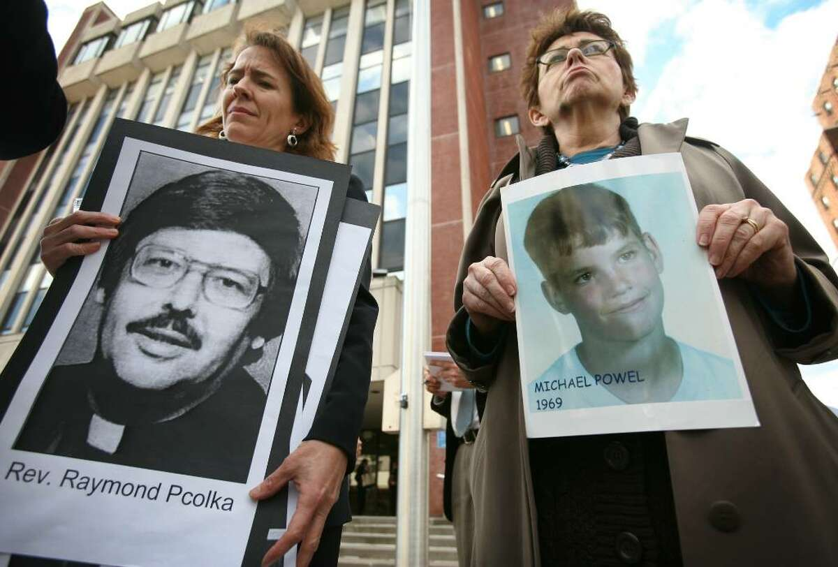 Anne Barrett Doyle, left, co-director of Bishop Accountability.org, holds a photo accused priest Raymond Pcolka, and abuse victim Gail Howard of Norwalk holds a photo of fellow victim Michael Powel, at a protest outside Bridgeport Superior Court on Thursday.